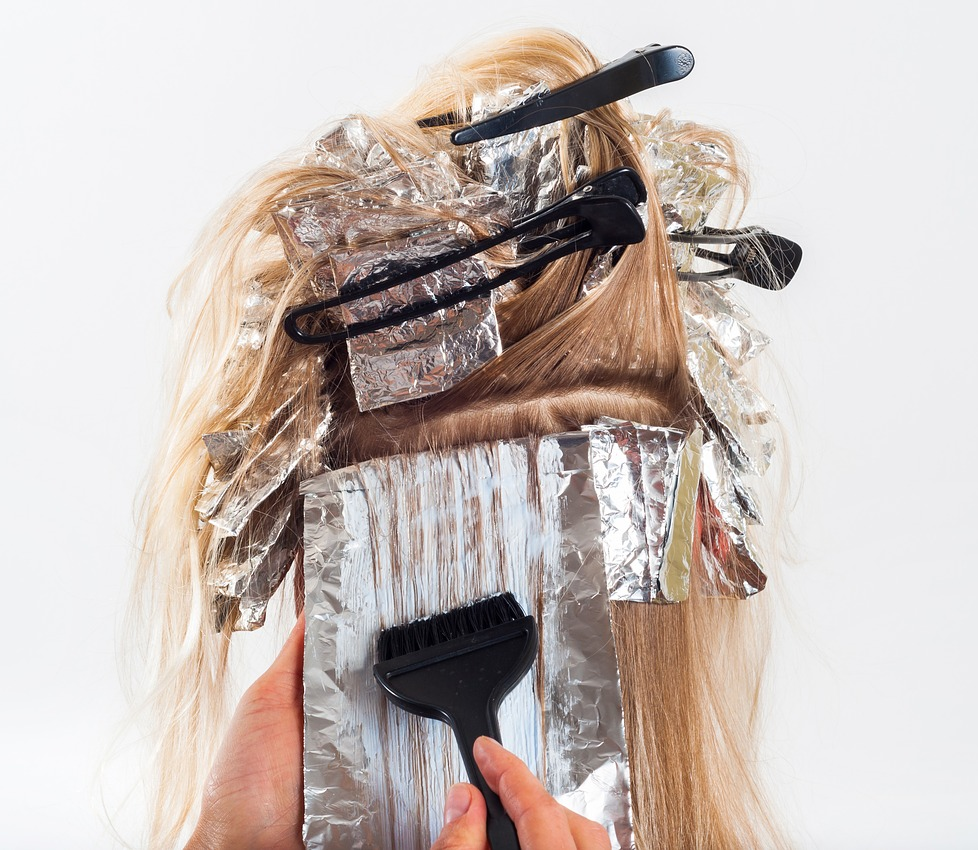 Photo of a hairdresser placing foils in hair