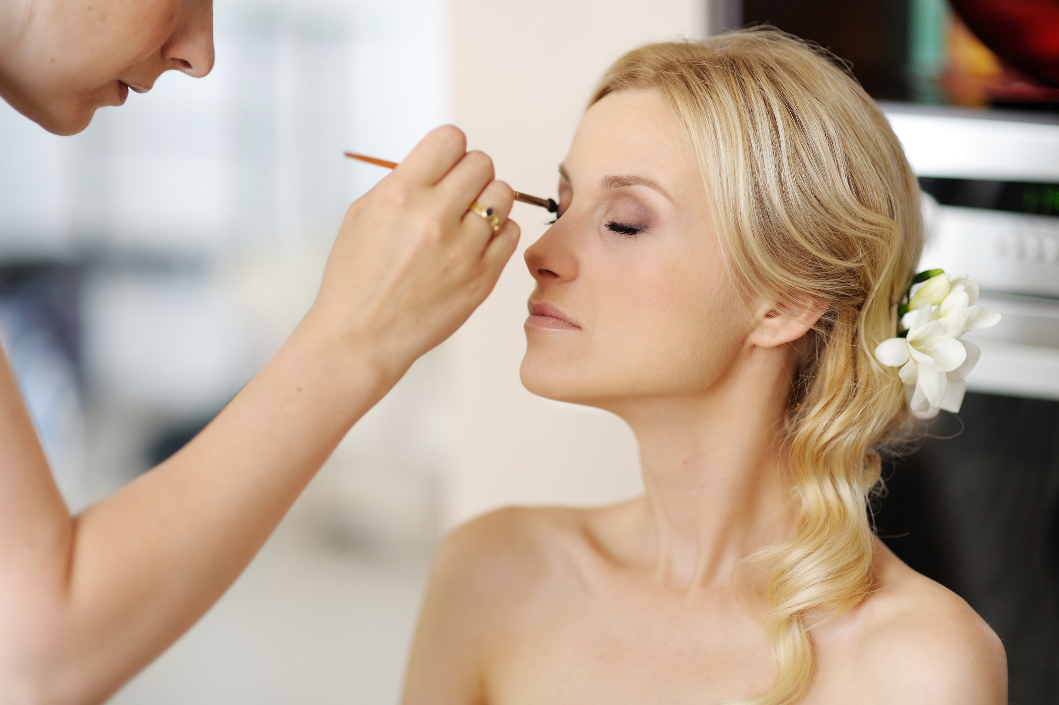 A photo of a woman having her makeup done